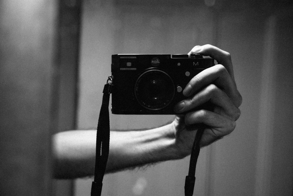 Hand holding Leica M type 240 in the mirror
